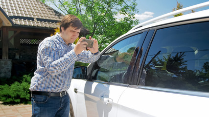 Young man making photos on smartphone of his car