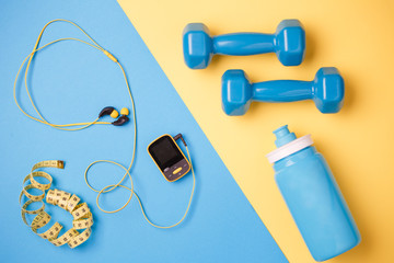 Photo of player, dumbbells, bottle of water, centimeter tape on blue and yellow background