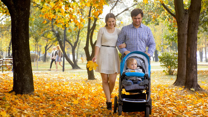 Happy young parents walking with 1 year old baby son sitting in pram at autumn park