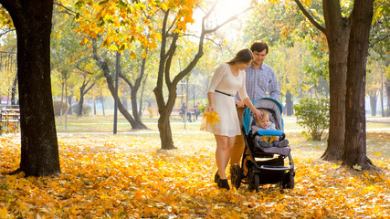 Beautiful young couple enjoying walking at autumn park with their 1 year old baby boy sitting in buggy