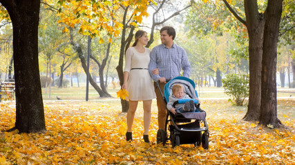 Happy smiling family with baby boy boy in pram walking on yellow leaves at autumn park