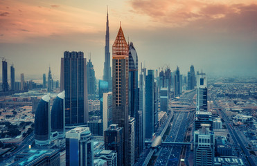 Aerial view on skyscrapers of Dubai, UAE, at sunset. Scenic cityscape with dramatic sky. Travel and architectural background.