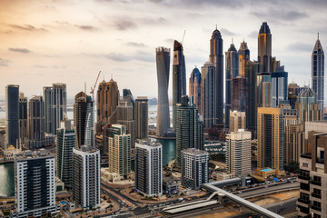 Futuristic architecture of Dubai Marina, UAE. Scenic skyline with famous world tallest skyscrapers in sunset light. Travel background.