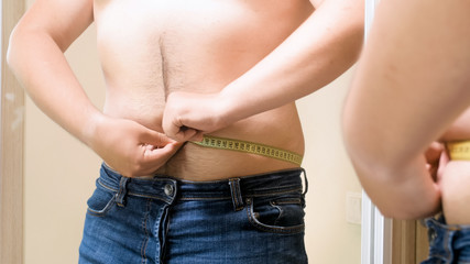 Closeup photo of overweight man with measuring tape at mirror