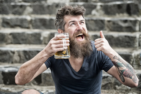Bearded man holds beer mug, drinks beer outdoor. Craft beer concept. Man with long beard looks relaxed, shows thumb up. Man with beard and mustache on happy face, stony background, defocused.