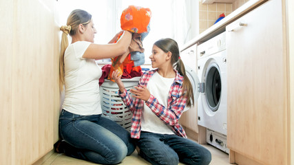 Beautiful young mother with daughter loading clothes in washing machine at laundry