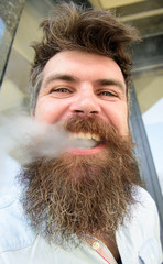 Hipster with tousled hair and gray on relaxed cheerful face with white smoke flying out of mouth. Man with beard and mustache smoking, building background. Vaping concept.