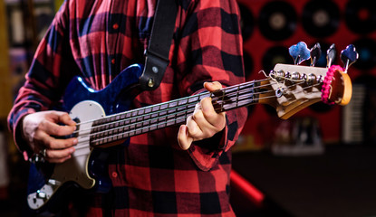 Male hands holds bass guitar, play music in club atmosphere background. Play guitar concept. Musician, artist play electric guitar musical instrument. Fingers clamp strings on bass guitar neck.