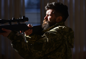 Man with beard wears camouflage clothing, dark interior background. Hunter, soldier with gun aiming before shooting. Shooter concept. Macho on suffering grimace face aiming at victim.