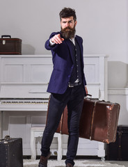 Man, traveller with beard and mustache with luggage, luxury white interior background. Baggage delivery concept. Macho elegant on strict face stands, holds suitcase, pointing forward.