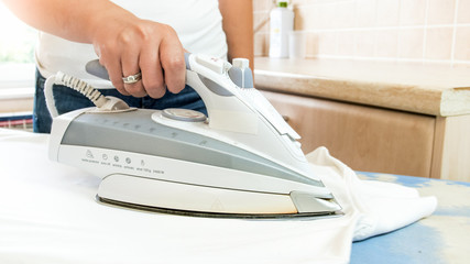 Closeup image of woman using electric iron at laundry