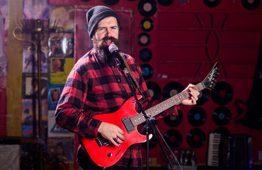 Musician with beard play electric guitar instrument. Frontman concept.
