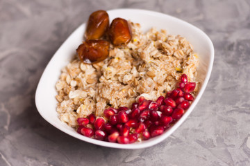 Cooked yummy warm oatmeal and heap of ripe fresh pomegranate seeds and three dried dates in white ceramic bowl on worn gray scratched concrete