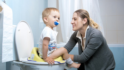 Young caring mother teaching her boy using toilet