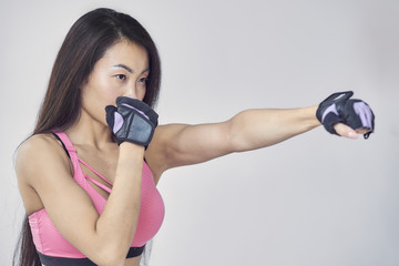 Asian woman boxing exercise with hands wrap. Beauty face and natural makeup sports bra outfit.