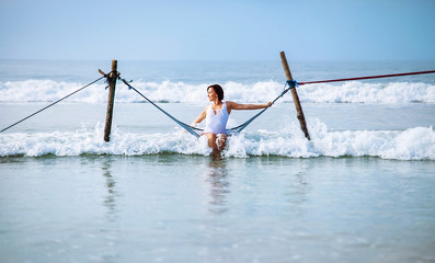 Woman in white swimsuit sits in hammock swing over the ocean surf line
