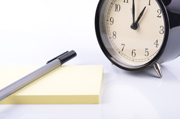 Listing memo and schedule concept,vintage alarm clock,pen  and yellow sticky notepad on table