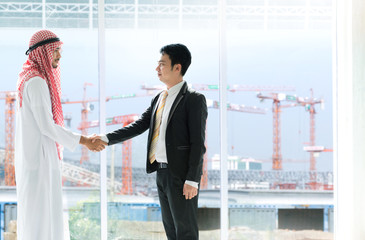 Arab business man shake hand with business man in the black suit near the window, with clipping path for background