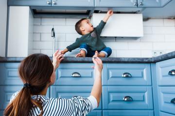 Toddler child in kitchen, children safety at home concept.
