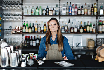 Portrait of confident female owner standing at checkout counter