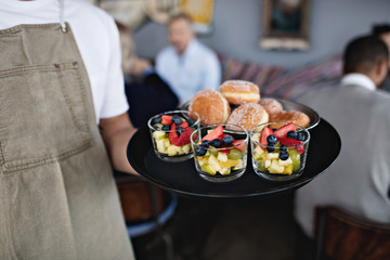 Midsection of owner holding food in serving tray at restaurant