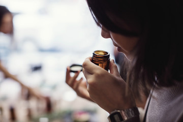 Young woman smelling perfume from bottle at workshop