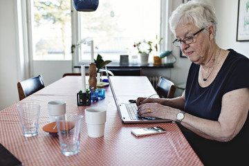 Senior woman using laptop while sitting at dining table in room