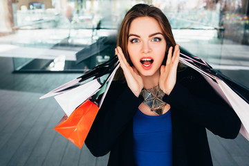 young trendy woman with shopping bags making a surprised face and looking at camera while standing against blurred background - shopping mal