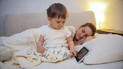 Cute little boy using digital tablet while his mother sleeping in bed