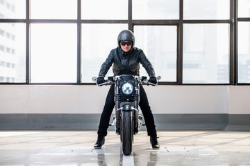 Portrait of man on electric cafe racer motorbike, inside garage