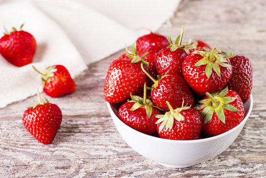 strawberry in a white bowl on a table