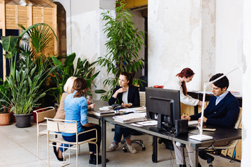 Group of of businesspeople working in office, three women in conversation at desk