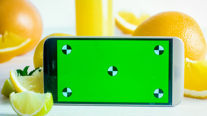 Closeup image of smrtphone with empty green screen on table next to citrus fruits. Perfect for young own image