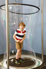 Little blond kid boy playing with huge soap bubbles construction indoors. Happy healthy smiling child having fun with experiments