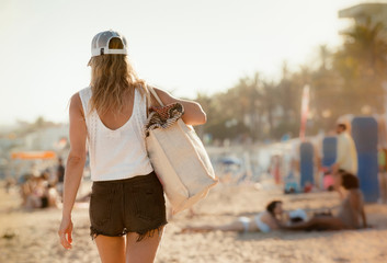 Woman walking along  beach, rear view, Sitges, Catalonia, Spain