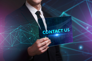 Business, Technology, Internet and network concept. Young businessman working on a virtual screen of the future and sees the inscription: Contact us