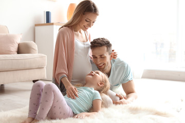 Young pregnant woman with her family at home