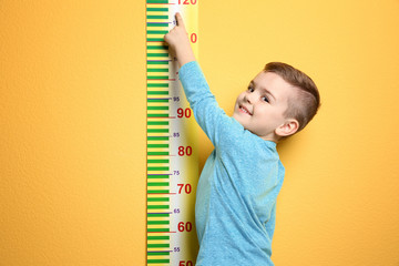 Little boy measuring his height on color background