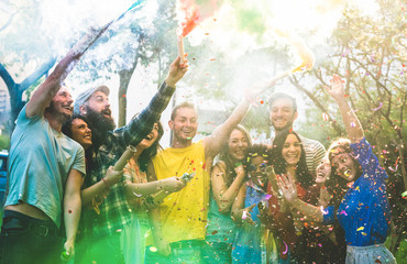 Happy friends having fun at garden party with multicolored smoke bombs outdoor - Young millennial students celebrating spring break together - Genuine youth concept - Focus on confetti and left people