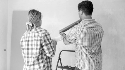 Black and white image of young couple choosing wallpapers for new home