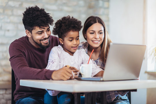 Girl and mixed race parents use laptop at home