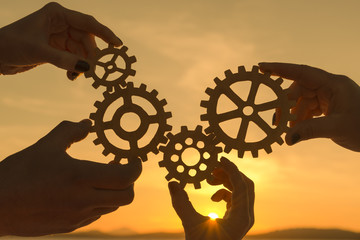 gears in the hands of people against the background of sunset. teamwork.