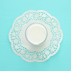 Top view image of milk over pastel wooden background. Symbols of jewish holiday - Shavuot.