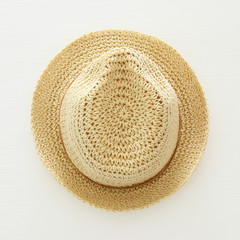 vacation and summer image with fedora beach hat over white wooden background.