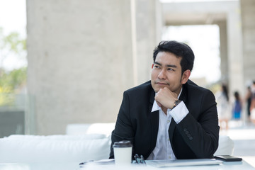 Thoughtful Asian businessman sitting in cafe with city background.