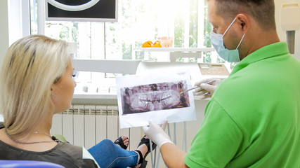 Closeup photo of doctor talking about teeth treatment and showing x-ray image to his patient