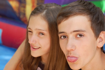 A boy and a teenage girl fooling in the school. They show tongues and smile