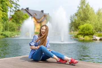 Young woman resting and having fun in the park sitting on a pier over the lake.