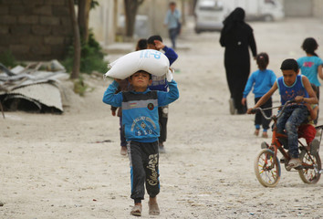 A boy carries food aid given by UN's World Food Programme in Raqqa