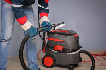 Man Vacuuming a Construction Site. Closeup of a cleaner in special clothes and rubber gloves holds a brush from an industrial professionally vacuum cleaner